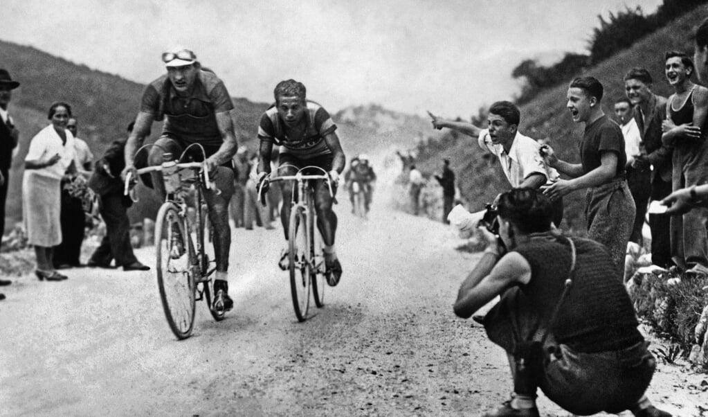 De Italiaanse wielrenners Gino Bartali (links) en Olimpio Bizzi op 24 augustus 1938 tijdens de Giro d'Italia.  (beeld afp)