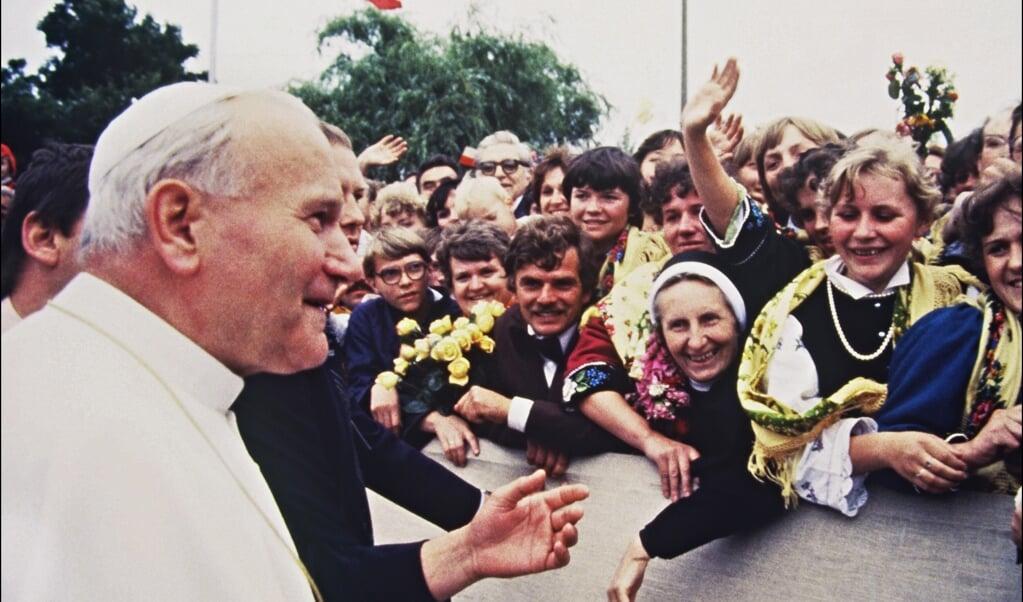 Paus Johannes Paulus II groet toegestroomde gelovigen tijdens zijn bezoek aan de Poolse hoofdstad Warschau op 11 juni 1983.  (beeld AFP)