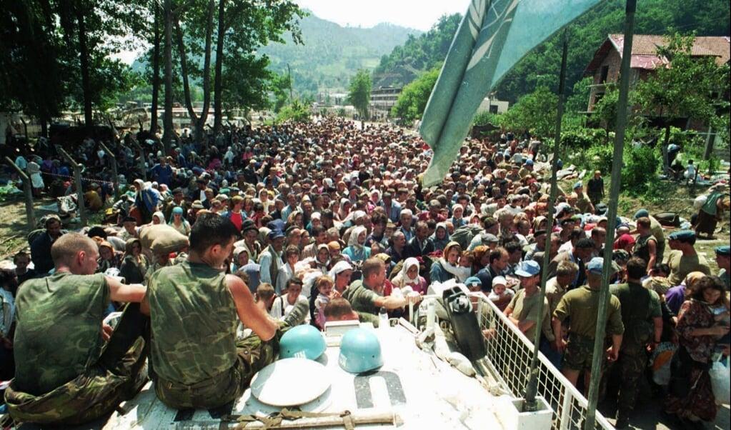 Nederlandse blauwhelmen zitten op donderdag 13 juli 1995 op hun voertuig terwijl moslimvluchtelingen uit Srebrenica zich verzamelen in het dorp Potocari, zo'n vijf kilometer ten noorden van Srebrenica.   (beeld hollandse hoogte / ap)