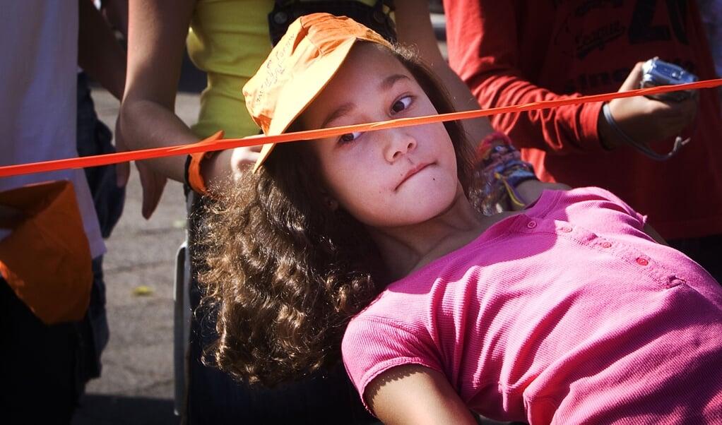 Een meisje danst de limbo tijdens een schoolactiviteit. Steeds minder kinderen spelen dagelijks buiten.  (beeld anp / Robin Utrecht)