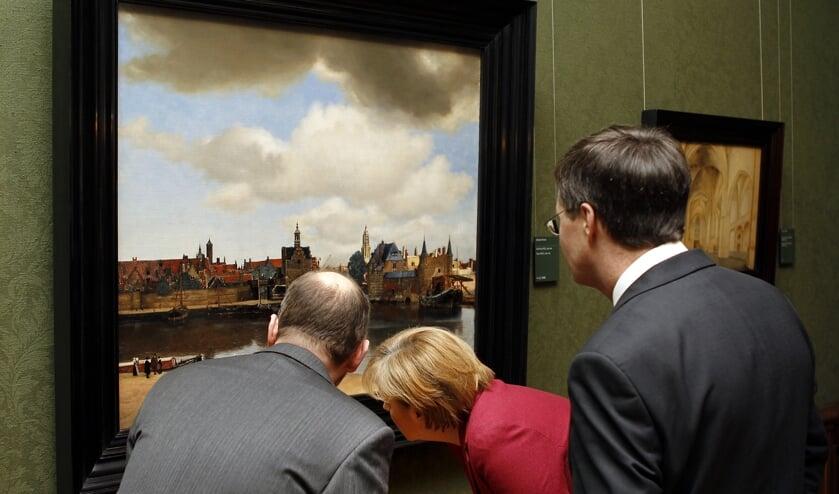 De Duitse bondskanselier Angela Merkel (rechts) bekijkt in 2010 het schilderij 'Gezicht op Delft' in het Haagse Mauritshuis.  (beeld anp / Robert Vos)