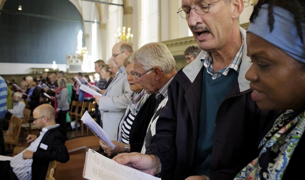 Tijdens de slotbijeenkomst van de vrijgemaakt-gereformeerde Schooldag in de Broederkerk in Kampen zingen honderden bezoekers Psalm 119 in de versie van Psalmen voor Nu. Het was soms happen naar adem.  (beeld Dick Vos)