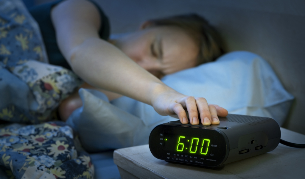 Young woman pressing snooze button on early morning digital alarm clock radio  (beeld istock)