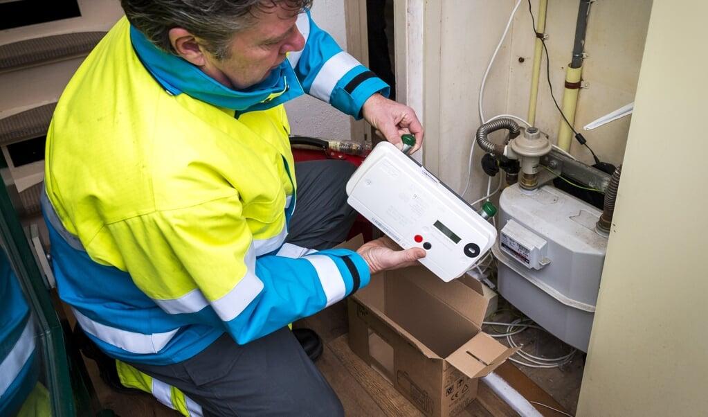 Een monteur installeert een slimme gasmeter. Wil je van het gas af, dan worden gasaansluiting en meter verwijderd, de rekening gaat naar de gasverlater.  (beeld anp / Lex van Lieshout)