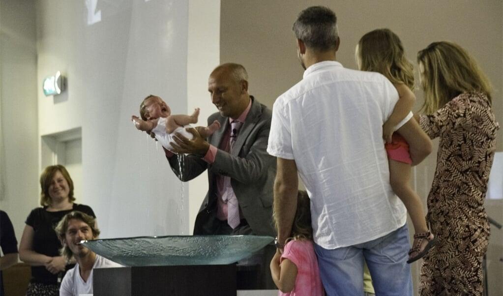 Dominee Atze Buursema uit Amersfoort doopt een baby door onderdompeling. 'Dopen betekent letterlijk onderdompelen.'  (beeld Carel Cramer)