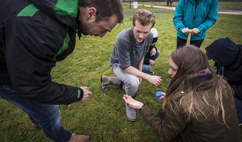 Studenten zoeken naar regenwormen tijdens een practicumles op het terrein van de universiteit.  (beeld anp / Alexander Schippers)