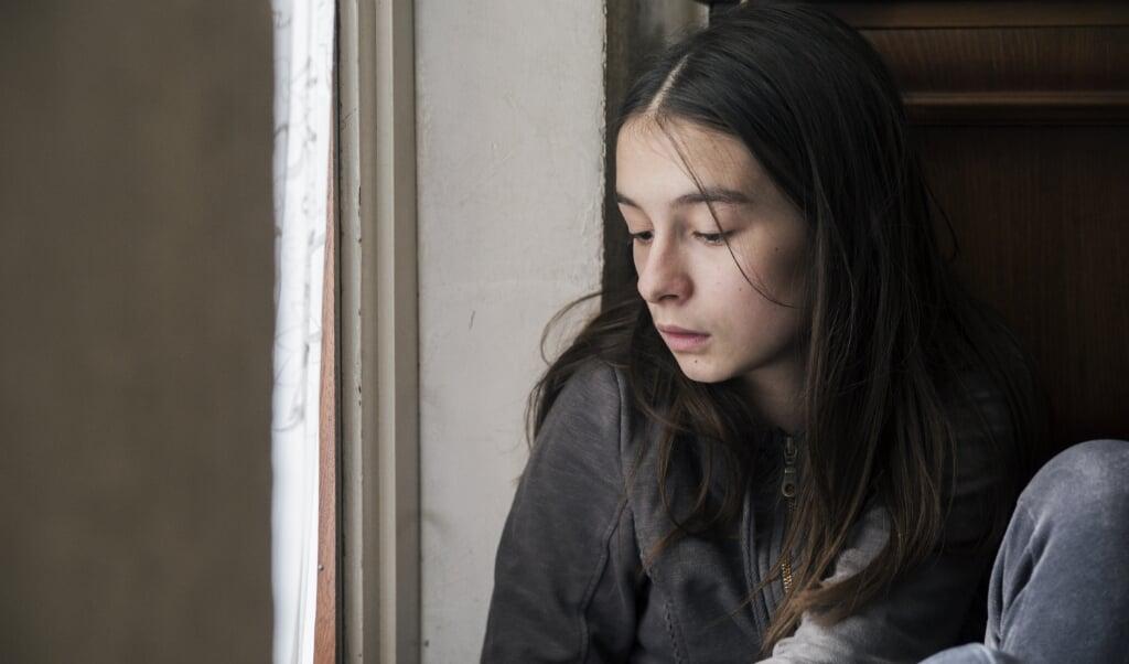 Photo of Sad girl looking out of window  (beeld istock)