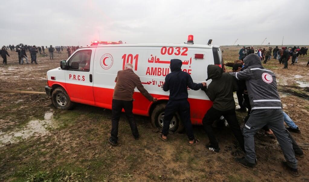 Archieffoto uit december 2018: Palestijnse demonstranten duwen een vastgelopen ambulance uit de modder.  (beeld afp/Mahmud Hams)