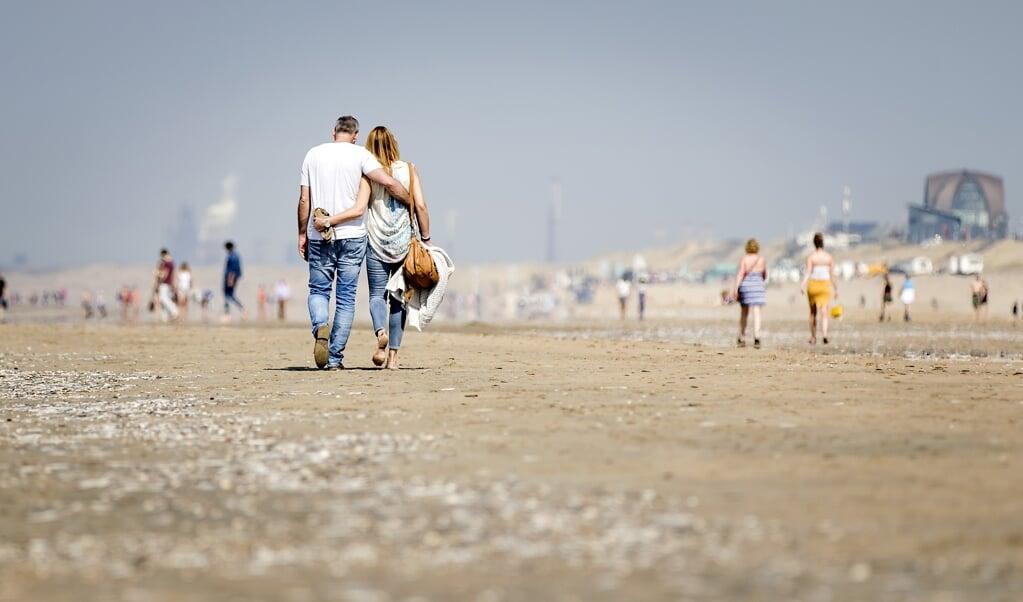 Badgasten lopen langs de kustlijn op een zonovergoten lentedag.  (beeld anp / Koen van Weel)