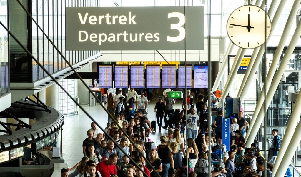 Reizigers in de vertrekhal op Schiphol op de drukste dag van het jaar.  (beeld anp / Remko de Waal)