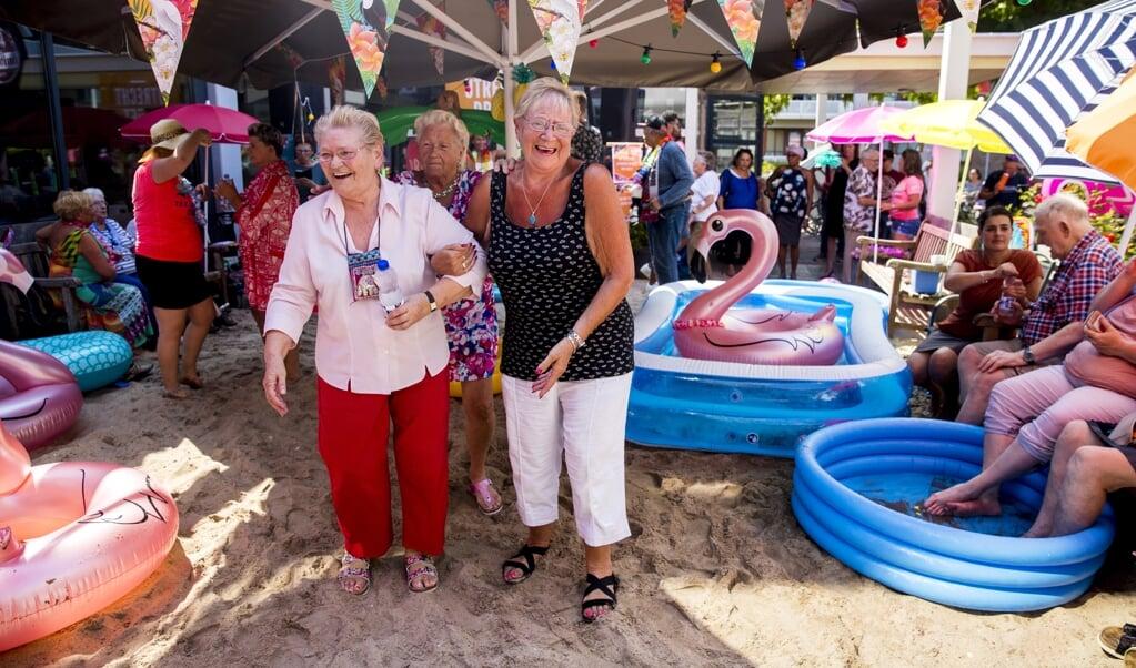Ouderen van een zorgcentrum in het Rotterdamse Crooswijk genoten tijdens een hittegolf in 2018 van het zomerse weer op een strandje dat speciaal voor hen was aangelegd.   (beeld anp / Jerry Lampen)