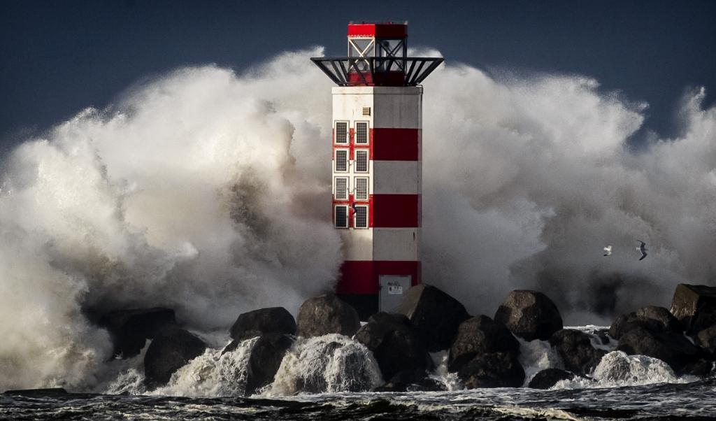 Grote golven slaan in IJmuiden tegen het baken op de kop van de pier tijdens stormachtig weer. Wetenschappers hebben plannen gemaakt om de Noordzee in te dammen in de strijd tegen een hogere zeespiegel.  (beeld anp / Koen van Weel)
