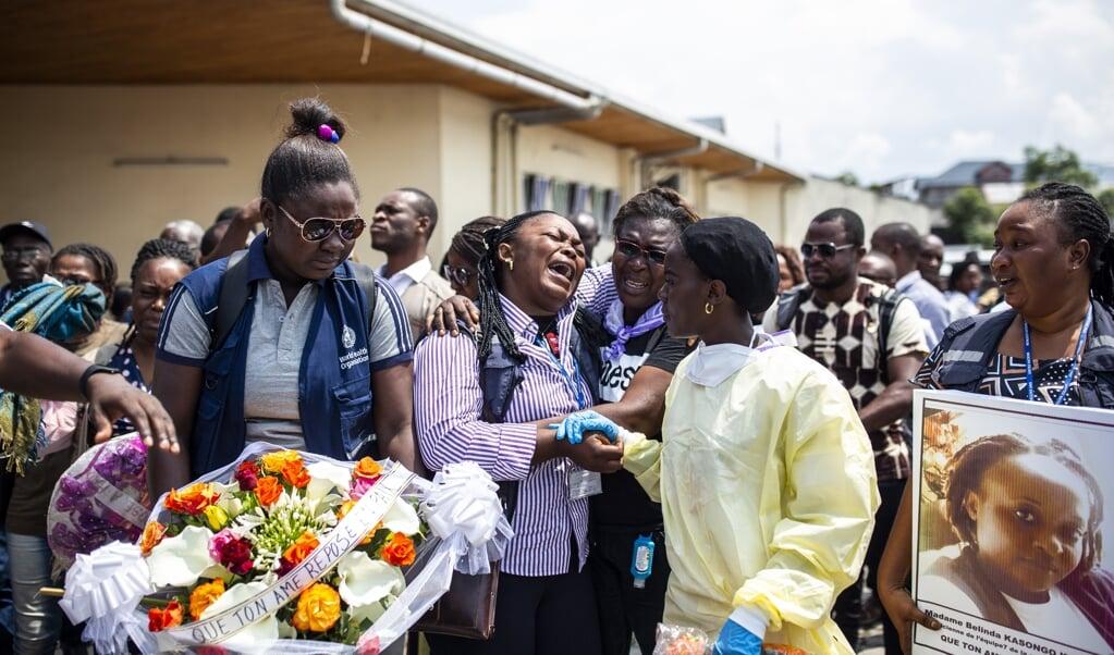 Familieleden rouwen op de begrafenis van een vermoorde ebolahulpverlener.  ( beeld afp / Patrick Meinhardt)