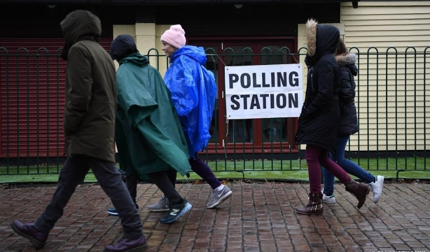 2019-12-12 09:10:31 epa08065182 Pedestrians pass a polling station in south London, Britain, 12 December 2019. Britons go to the polls on 12 December 2019 in a general election to vote for a new parliament.  EPA/ANDY RAIN  ( beeld anp)