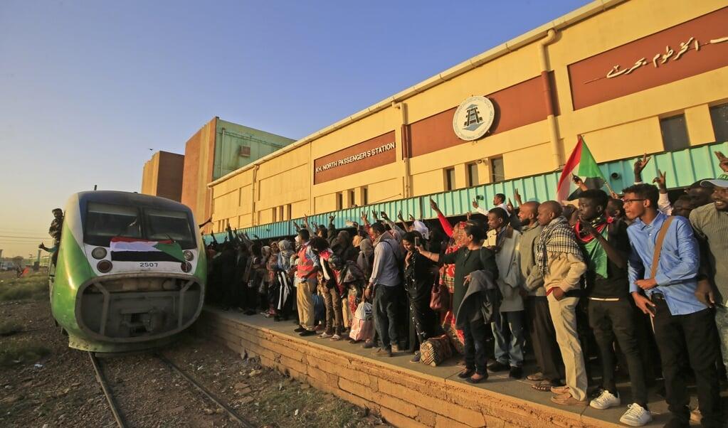 Sudanezen wachten op de trein die hen naar Atbara zal brengen, voor een feestelijke herdenking van de protesten van vorig jaar.  ( beeld afp / Ashraf Shazly)