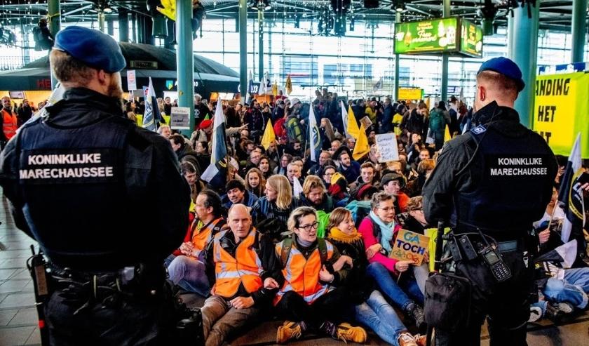 2019-12-14 12:20:47 SCHIPHOL - Actievoerders van Greenpeace protesteren in de hal van de luchthaven tegen de in hun ogen grote vervuiler Schiphol. ANP ROBIN UTRECHT  ( beeld anp)