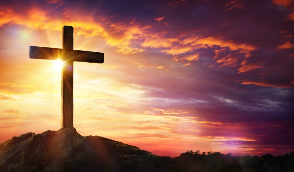Cross At Sunset With Sunlight And Orange Clouds  ( beeld Getty Images/iStockphoto)