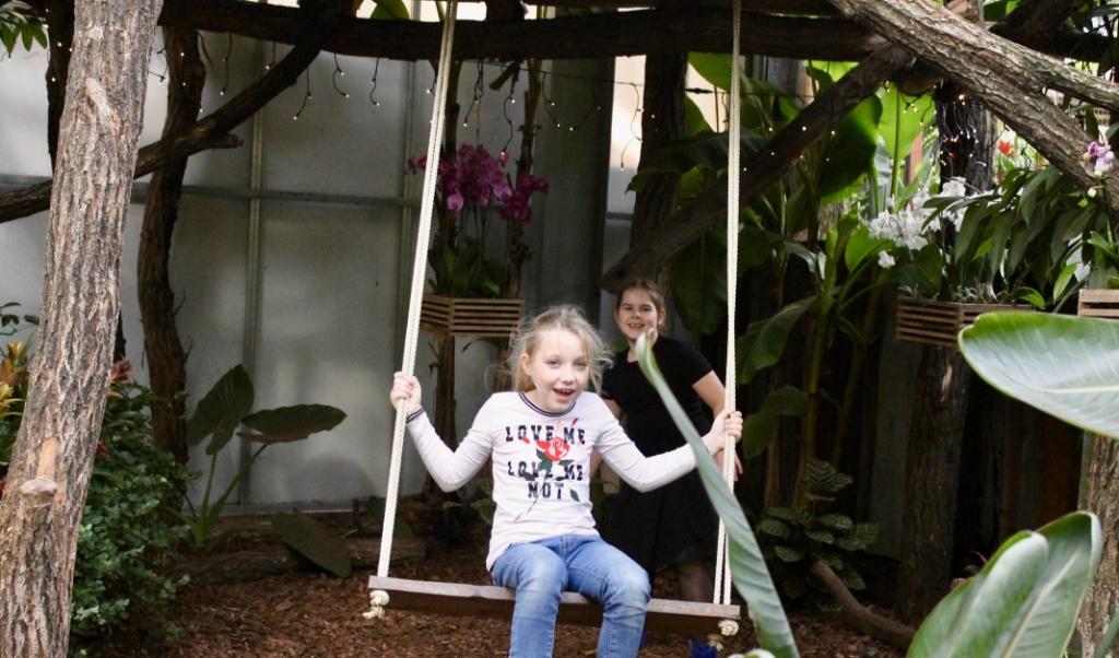 Kayleigh op de schommel en Ella duwt haar.  ( beeld Jannelie Bras)