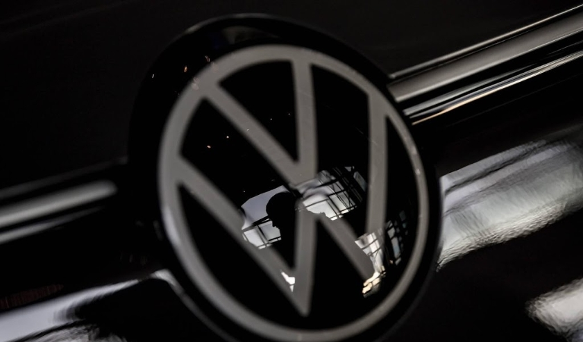 2019-11-19 13:30:29 epa08008734 A visitor is seen through a Volkswagen (VW) logo at Volkswagen Glaeserne Manufaktur (Transparent Factory) in Dresden, Germany, 19 November 2019. The German car automaker Volkswagen plans to invest 60 billion euros to switch  ( beeld anp)