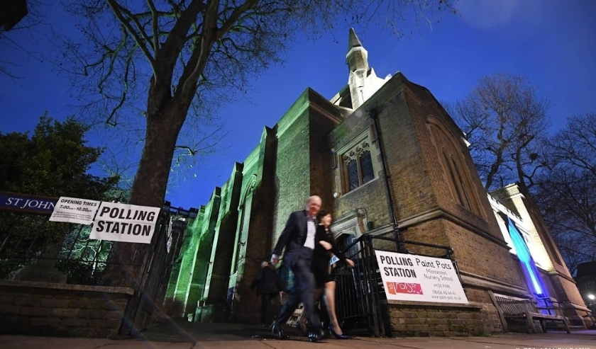 2019-12-12 07:18:30 epa08064297 A couple depart St. Johns church after voting during the general elections in London, Britain, 12 December 2019. Britons will go to the polls on 12 December 2019 for a general election to vote for a new parliament.  EPA/AND  (beeld anp)