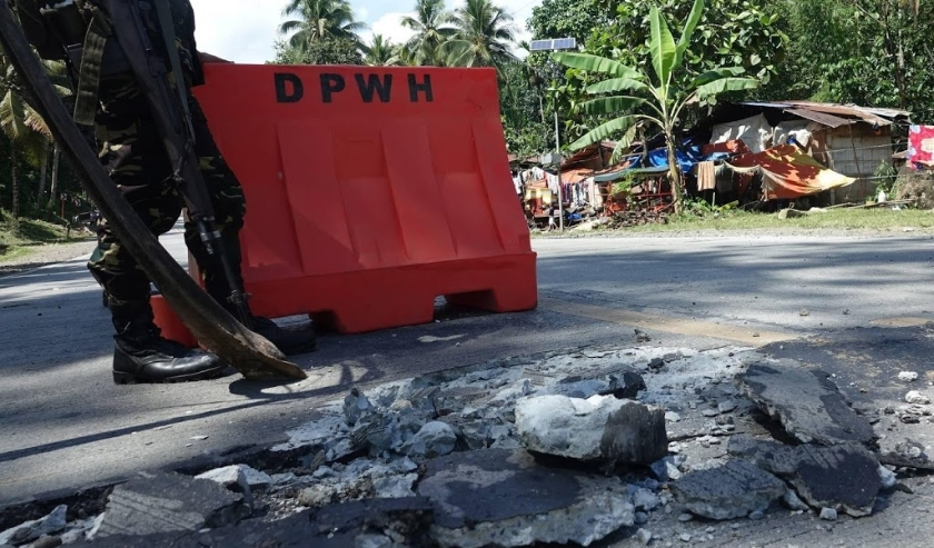 2019-10-31 11:30:48 epa07962195 A Filipino soldier stands guard at a damaged road in the aftermath of a 6.5 magnitude earthquake, in the town of Malasila, Cotabato province, Philippines, 31 October 2019. According to the United States Geological Survey (U  ( beeld anp)