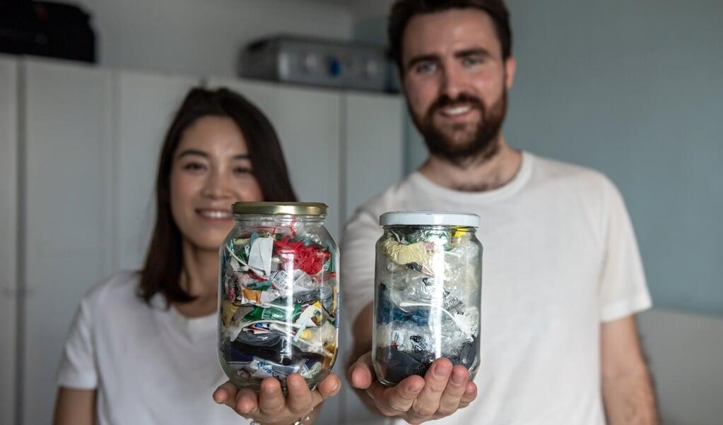 Carrie Yu en Joe Harvey, oprichters van een afvalvrije winkel in Peking, hebben het afval dat ze in drie maanden tijd hebben verzameld in twee potten gestopt.  (beeld afp / Nicolas Asfouri)