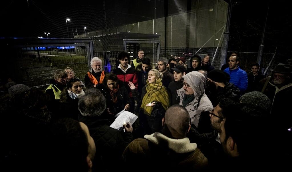 Deelnemers aan de wake, maandagavond, voor een Iraans gezin zingen bij Kamp Zeist in het Farsi een lied.  (beeld Jeroen Jumelet)