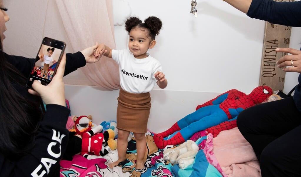 Quenisha is twee jaar en heeft op Instagram minstens 369.000 volgers. Ze heeft zelfs haar eigen boekingsagent en staat ingeschreven bij kindermodellenbureau Kidz Management. Sunisa (30), de moeder van Quenisha, maakt vrijwel dagelijks nieuwe foto's, terwi  (beeld Martijn van de Griendt / Document Nederland)
