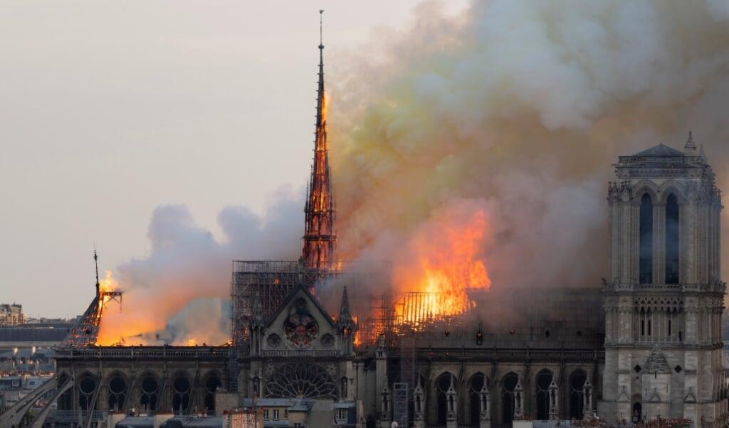 De brandende Notre-Dame in Parijs, op 15 april 2019, met de brandende centrale torenspits die daarna zou instorten.  (beeld Fabien Barrau / afp)