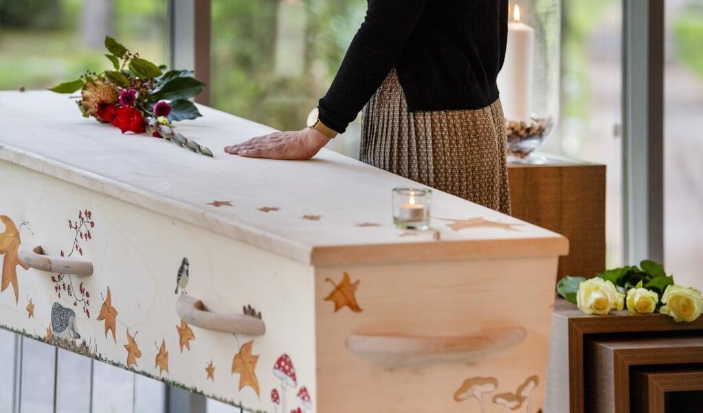 Nabestaande neemt afscheid bij de doodskist van een overledene in een uitvaartcentrum.  (beeld anp / Xtra Piroschka van de Wouw)