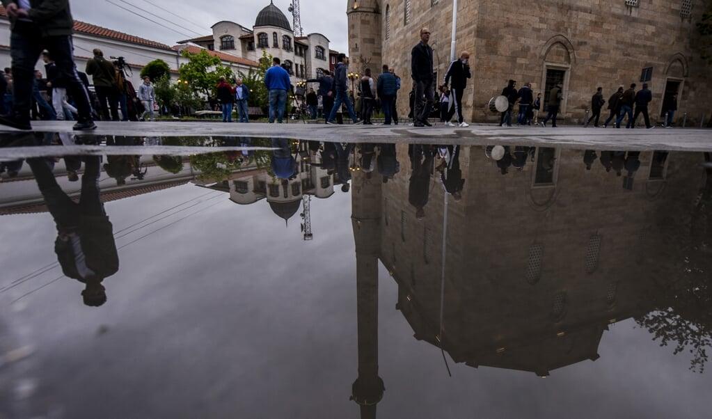 Moslims bij de grote moskee van de Kosovaarse stad Pristina. De overheid heeft imams gevraagd mee te werken aan deradicalisering van ISIS-strijders die in de gevangenis zitten.   ( beeld AFP)