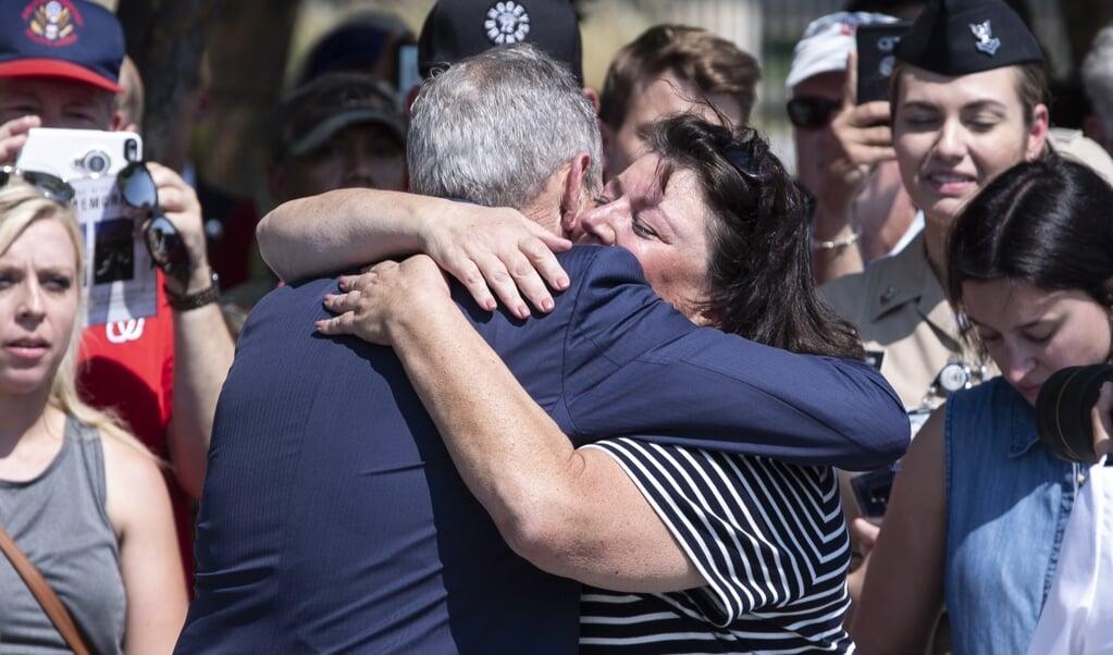 Oud-president George W. Bush wordt omhelsd door Lisa Dolan, weduwe van de bij de aanslagen van 9/11 omgekomen kapitein Robert Dolan. Bush riep de Amerikanen op, nu in de coronacrisis net als toen vereend te zijn.  (beeld Epa/michael Reynolds)