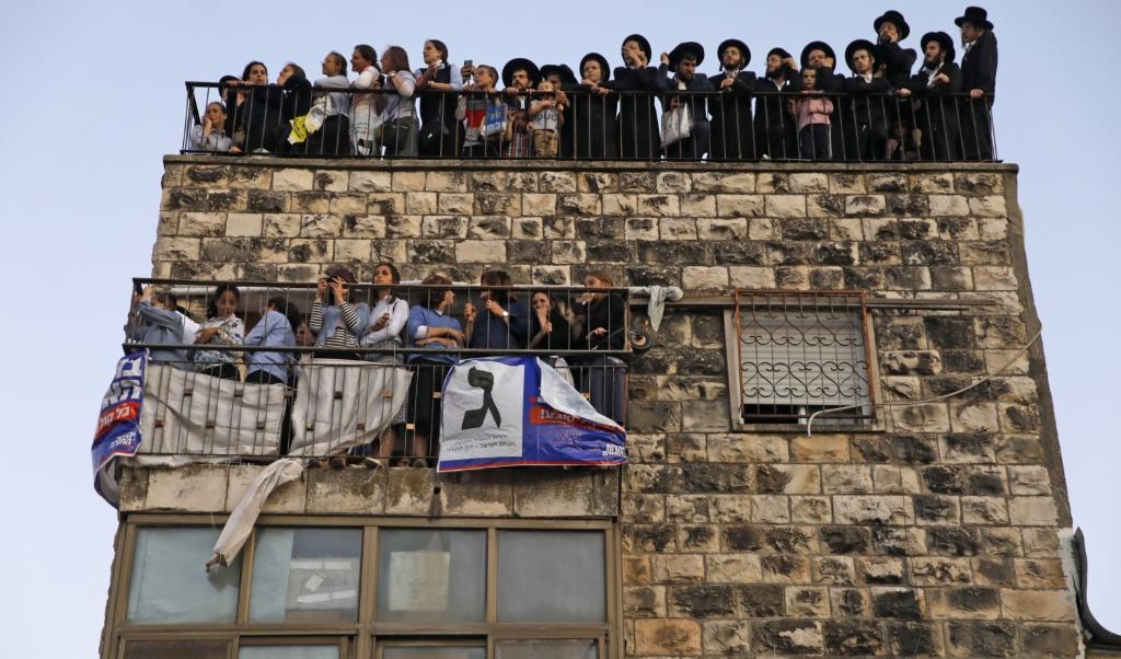 Orthodoxe Joden kijken toe bij een verkiezingsbijeenkomst in Jeruzalem.   ( beeld afp / Menahem Kahana)