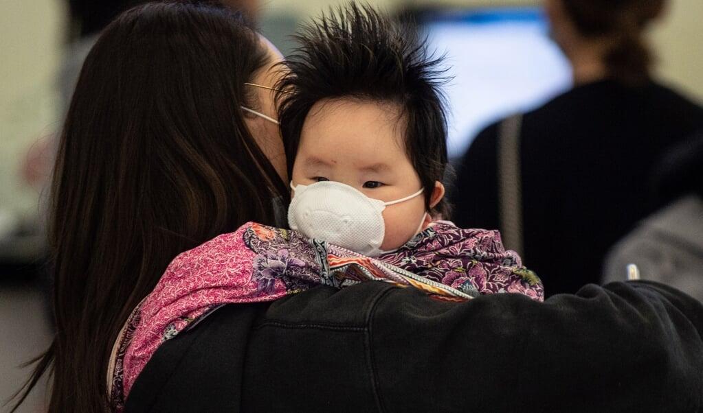 Een vrouw in Hongkong heeft haar kind een mondkapje voorgedaan, in januari dit jaar. Tegen het coronavirus werden meteen strenge maatregelen genomen, vanwege het collectieve SARS-trauma, maar ook vanuit gemeenschapszin.  (beeld afp / Philip Fong)