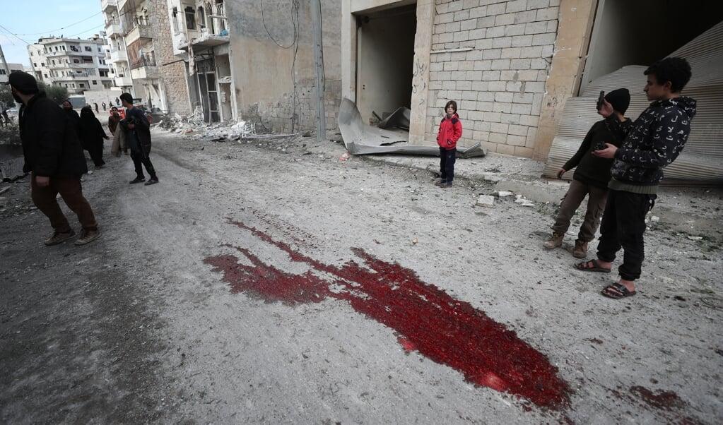 Syrische kinderen kijken naar een plas bloed na een luchtaanval op Ariha, een stad in de provincie Idlib, die tenminste negen burgers het leven kostte.  ( beeld anp)