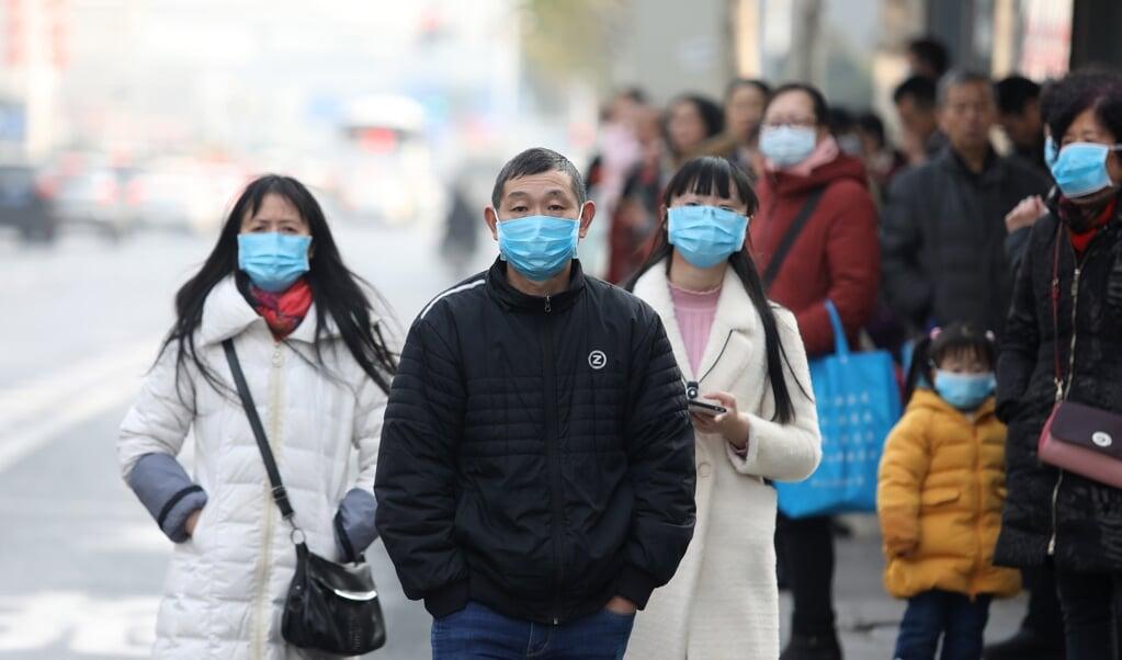 Chinese inwoners dragen maskers in de buurt van de vismarkt in Wuhan, waar veel besmettingen met het coronavirus zijn gemeld.   (beeld epa)
