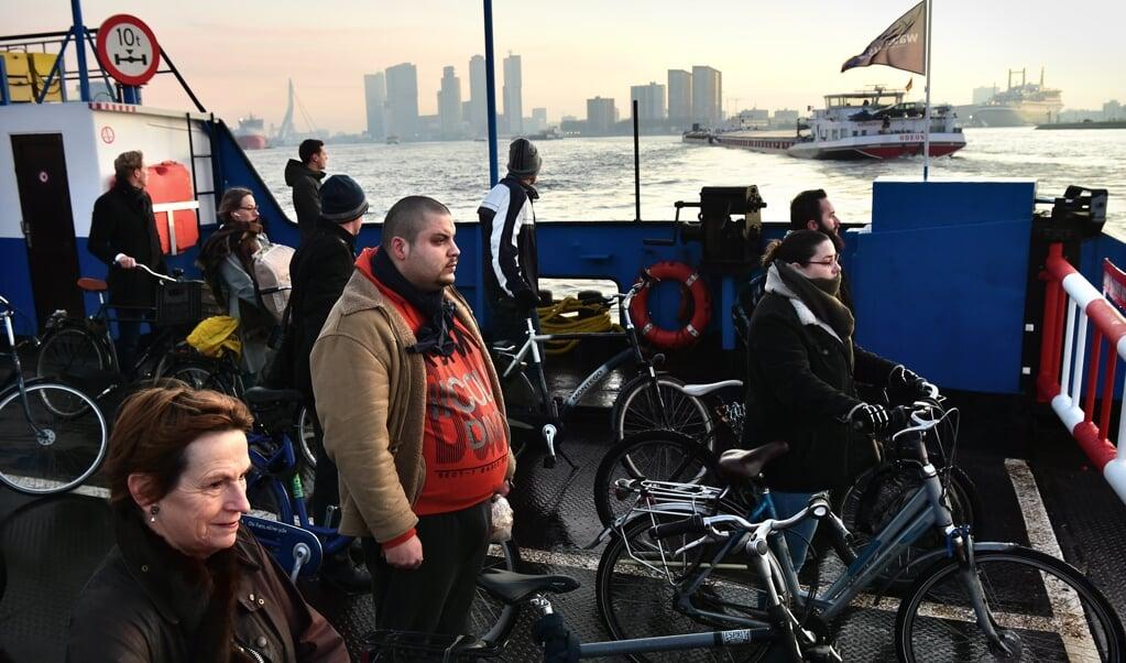 Fietsers en voetgangers op de tijdelijke pont over de Maas in Rotterdam. Aan de horizon de Erasmusbrug en de Kop van Zuid.  (beeld   Marcel van den Bergh)