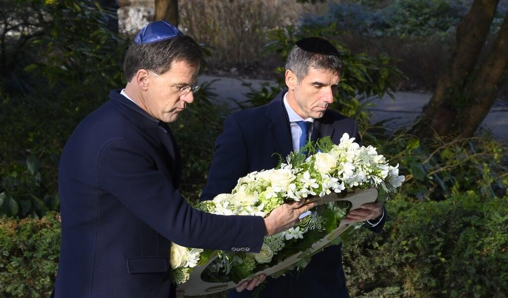 Minister-president Mark Rutte (links) en staatssecretaris Paul Blokhuis leggen een krans bij het Spiegelmonument Nooit meer Auschwitz tijdens de Nationale Holocaust Herdenking.  (beeld  anp / Evert Elzinga)