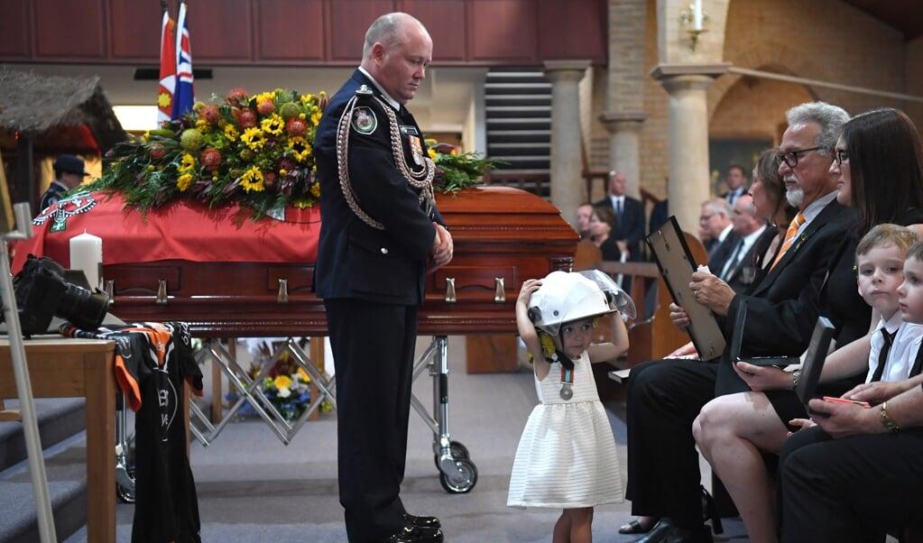 De Australische Charlotte O'Dwyer (1) draagt de brandweerhelm van haar vader Andrew, tijdens zijn begrafenis.   (beeld EPA)