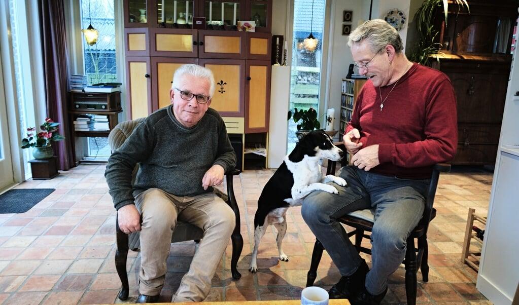 Pleegvaders Rik Laernoes (links) en Adriaan Rodenburg met hun hond Fonz, de grote liefde van John, die zelf niet op de foto wilde. Een verhaal over hem vond hij best.  (beeld  Dick Vos)