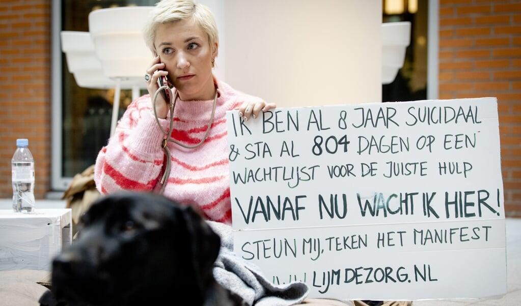 Charlotte Bouwman protesteert tijdens Blue Monday in de hal van het ministerie van Volksgezondheid, Welzijn en Sport tegen de wachtlijsten in de GGZ.  (beeld  anp / Sem van der Wal      )
