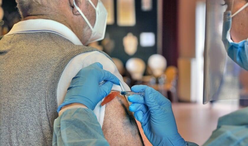 <p>Een oudere man haalt een griepprik in Berg en Dal.</p>  (beeld anp / Flip Franssen)