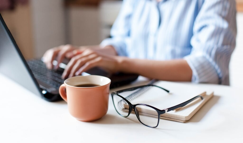 Remote working from home. Freelancer workplace in kitchen with laptop, cup of coffee, spectacles. Concept of distance learning, isolation, female business, shopping online. Close up of woman hands.  (beeld iStockphoto)