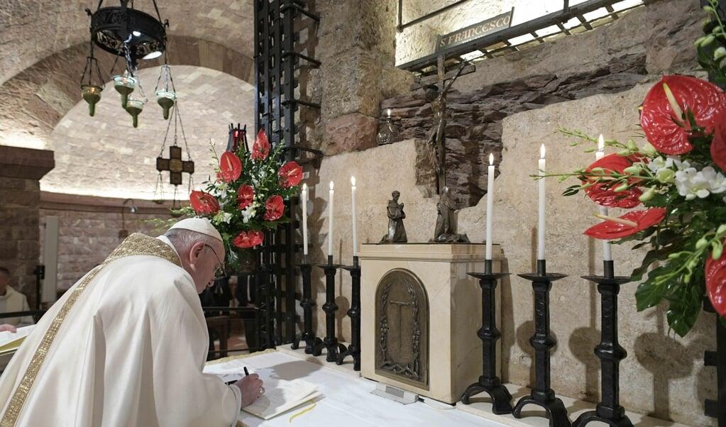 <p>Paus Franciscus ondertekent bij het graf van Franciscus van Assisi zijn nieuwe encycliek &#39;Fratelli Tutti&#39;. VATICAN MEDIA / AFP</p>  (beeld Handout / Vatican Media / afp)
