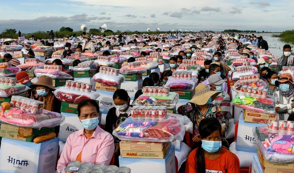 <p>Overlevenden van overstromingen in de Cambodjaanse provincie Banteay Meanchey ontvangen op 21 oktober noodhulp namens president Hun Sen.<em></em></p>  (beeld str / afp)