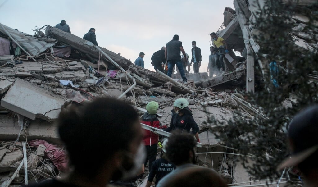 <p>Vrijwilligers zoeken naar overlevenden onder het puin in de Turkse stad Izmir.</p>  (beeld afp / Mert Cakir)