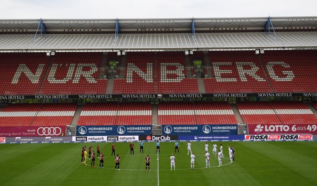 Spelers houden in het stadion van FC Nürnberg een minuut stilte voor de slachtoffers van corona.  (beeld epa / Matthias Hangst)