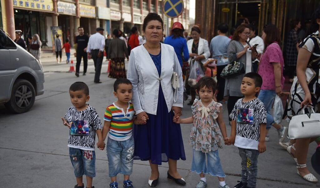 <p>Archieffoto uit juni 2019 van een Oeigoerse met kinderen op straat in Kashgar in de Chinese provincie Xinjiang.</p>  (beeld afp / Greg Baker)