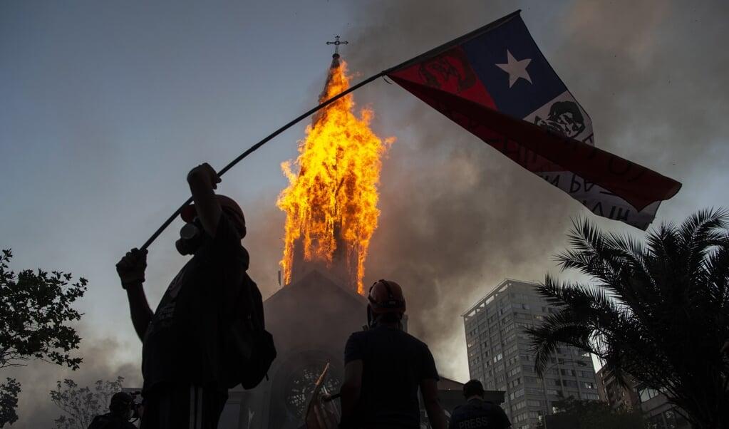 <p>Een actievoerder met de Chileense vlag bij de brandende toren van de kerk van Asuncion in Santiago, Chili. </p>  (beeld afp / Martin Bernetti)