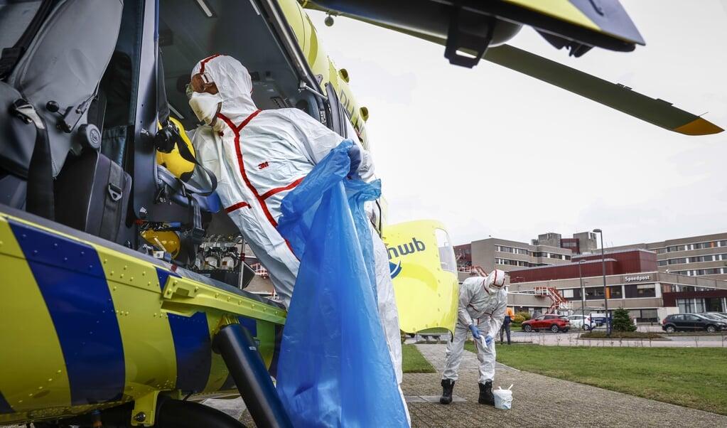 ALMELO - De Lifeliner 5, een traumahelikopter die speciaal is ingericht voor snel vervoer van intensive care-patienten, wordt ontsmet na het vervoer van een slachtoffer van het coronavirus van het Erasmus MC naar het ZGT. In het voorjaar is deze traumahelikopter ook ingezet voor coronavervoer in Nederland en Duitsland. ANP VINCENT JANNINK  (beeld Vincent Jannink)